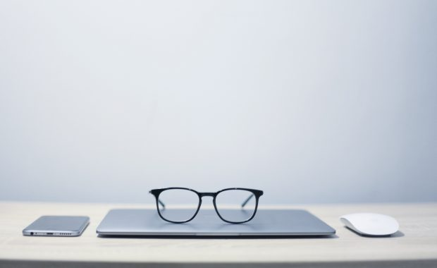laptop on clean desk with black rimmed glasses