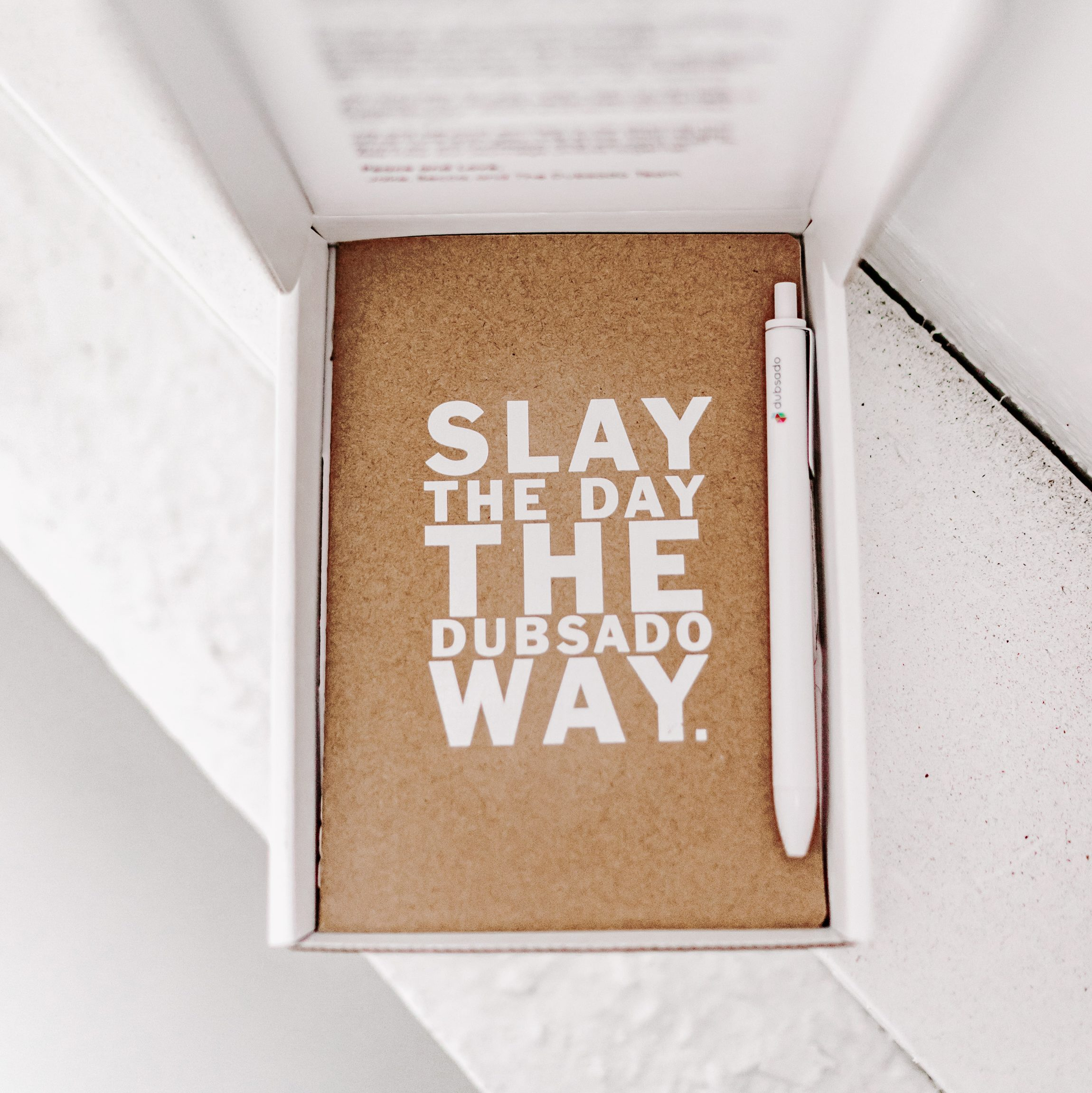 """Open white box with a dubsado branded pen and a notebooks that says """"Slay the day the Dubsado way"""" inside."""
